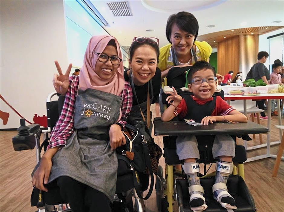 Yap (in yellow) and her husband founded WeCareJourney partly because their son Branden Lim (right) has spinal muscular atrophy (SMA). Pictured are programme participant Ainaa Farhanah Amali (left) and volunteer Poh Choo.