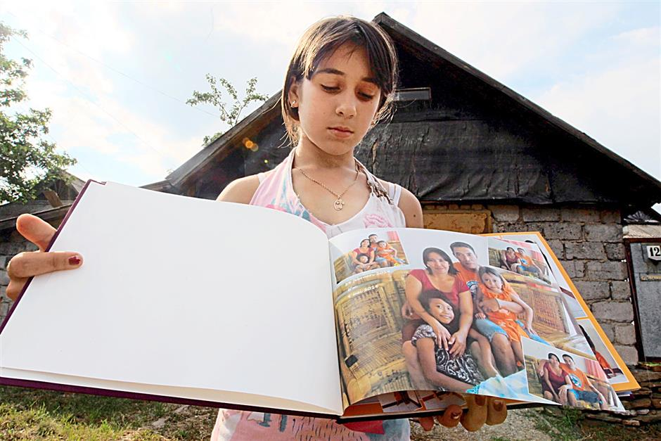 Demura Ksenia, 13, from the village of Petropavlovka near Grabovo showing a photo album that may have belonged to an Indonesian family. According to locals here, the photo album fell from Malaysia Airlines flight MH17, landing on its own in a garden here..starpic by kamarul ariffin/230714/Ukraine.