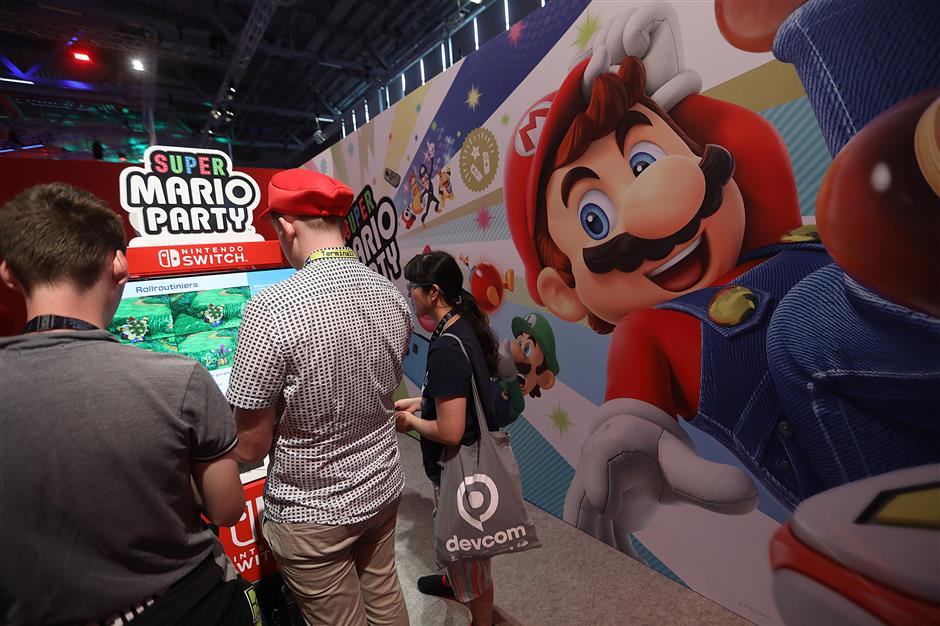 Gamers play the \'Super Mario Party\' computer game on a Nintendo \'Switch\' console at the Nintendo Co. stand at the Gamescom gaming industry event in Cologne, Germany, on Tuesday, Aug. 21, 2018. Gamescom is Germany\'s largest congress revolving around digital games, and acts as an interface with other cultural and creative branches, as well as with the digital economy according to their media site. Photographer: Krisztian Bocsi/Bloomberg