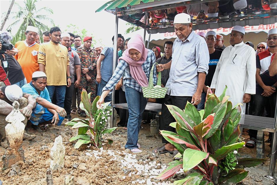 Painful goodbye: Nurul paying her last respects to Muhammad Adib at his grave while his father Mohd Kassim (second from right) and others look on at Kampung Tebengau in Kuala Kedah.