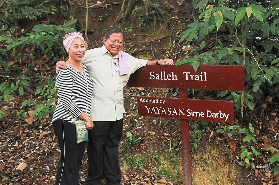 Salleh (right) and his wife Puan Sri Nor Aini Zainol Rashid at the beginning of the trail named after him for his efforts in conserving the environment.
