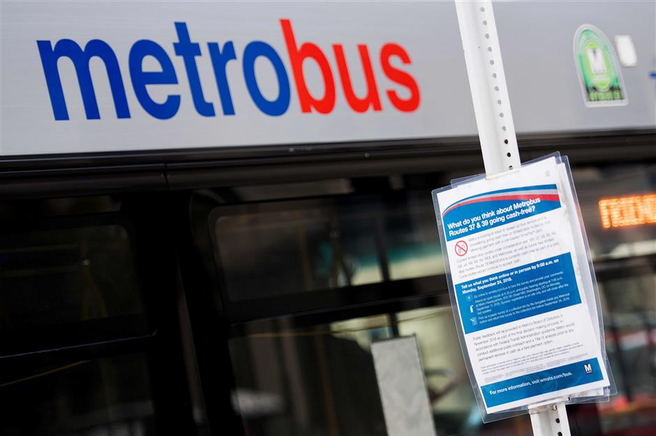 A sign asking about cash free bus rides is posted at a Metrobus stop in Washington, DC, on October 24, 2018. - As the US capital traded stifling summer heat for cool autumn breezes, signs began appearing on lamp posts, asking Washington commuters: what do you think about buses going cash-free? It was the latest iteration of a growing trend in the United States: from lunch spots to music venues and vendors at the city's ballpark, one Washington business after another are completely ditching paper for plastic. (Photo by Jim WATSON / AFP)