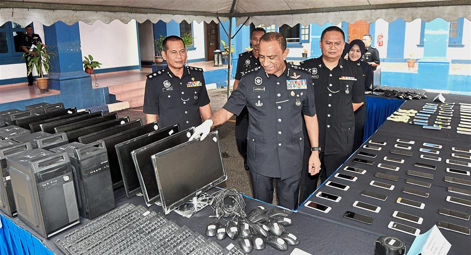 Johor police chief Comm Datuk Mohd Khalil Kader Mohd (middle) showing Macau Scam seized items after giving a press conference at the Johor Baru South Police District headquarters in Johor Baru on June 25.
