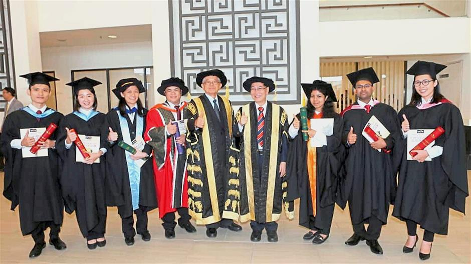 Dr Ting (centre) and the universityu2019s president Datuk Dr Chuah Hean Teik (fourth from right) with graduates at Utaru2019s convocation ceremony in Bandar Baru Kampar, Kampar.u2014 Photo courtesy of China Press.