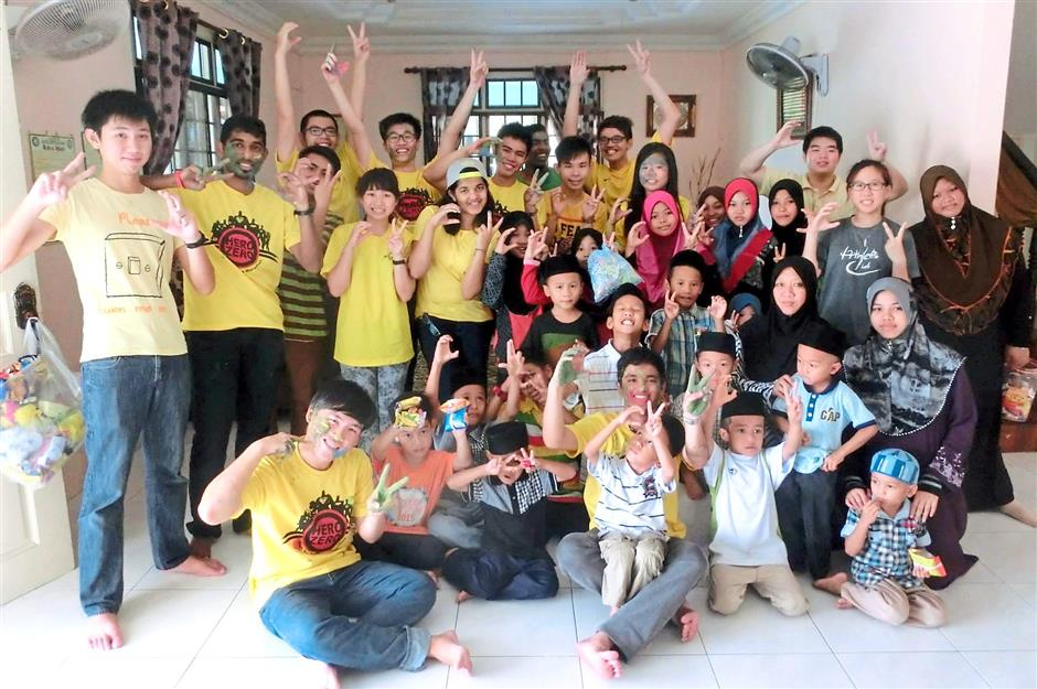 Curtin Sarawak students posing for a photo with orphans of the Rumah Anak Amal in Miri during a recent visit. Pic by curtin student.