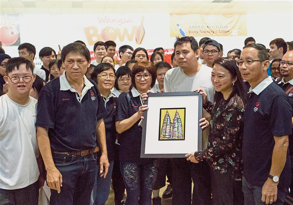 Yeoh (second from right) receiving a memento from Wong ( centre) and Special Olympics Selangor athlete Tan Sin Kit who created the painting.