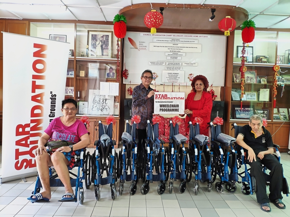 Rozaid (standing, left) handing over eight wheelchairs to Khatijah of Selangor Cheshire Home in Selayang.