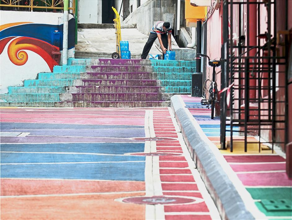 A man painting the steps in one of the city's backlanes.
