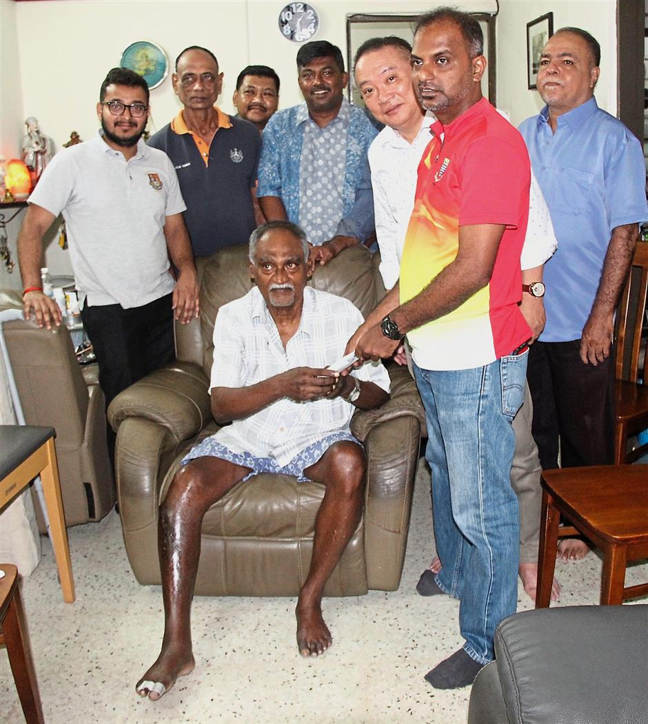 Jayanandhan (red jersey) handing the RM10,000 to Rajendran at his Island Glades home.