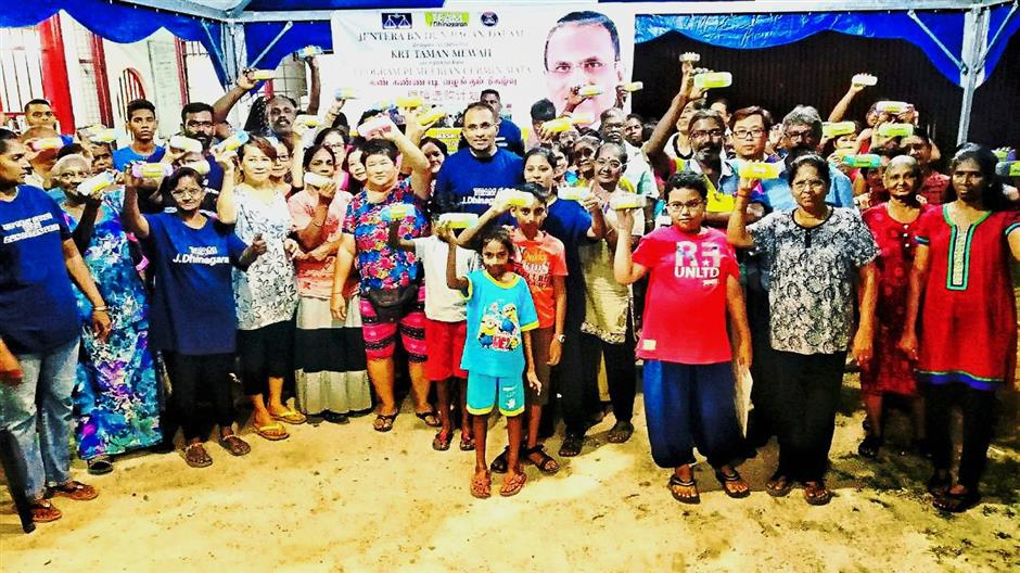 Dhinagaran (middle) with recipients of the free spectacles programme in Taman Mewah, Butterworth.