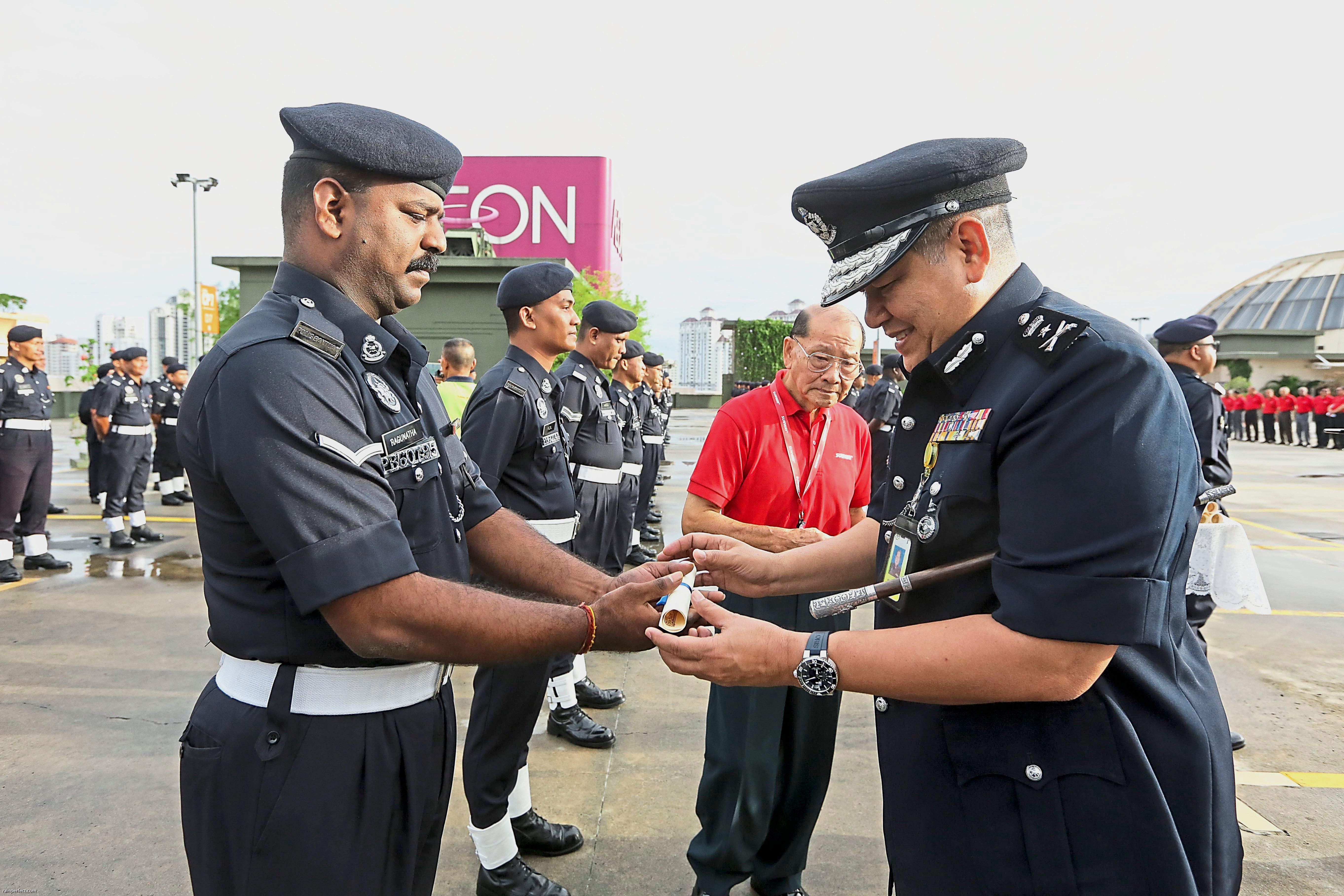 SAC Moktar handing  letters of empowerment to selected members of Sunway Groupu2019s  auxiliary police  contingent.