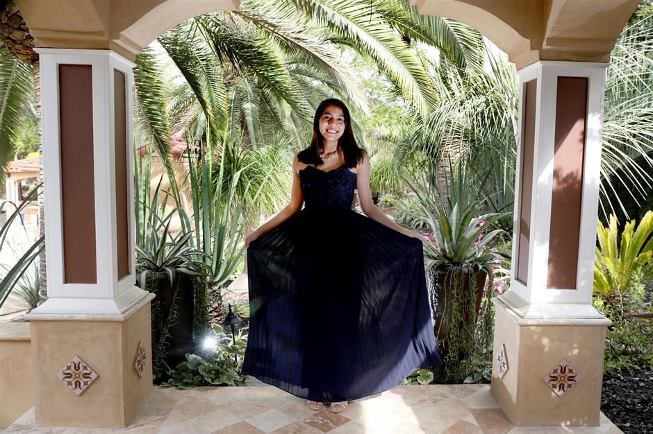 Nishka Ayyar, 16, poses with a prom dress at her home in Saratoga, Calif., on Wednesday, April 18, 2018. The junior high school students built the PromElle app designed for renting prom dresses to and from their users. (Ray Chavez/Bay Area News Group/TNS)