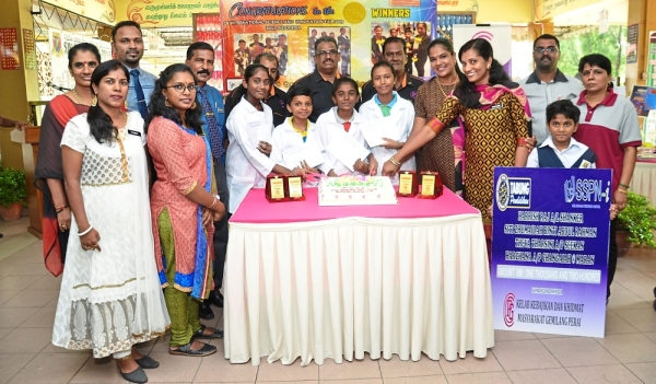 SJK (T) Ladang Prye pupils (in white coats from left) Siti Zhumaidah, Harrish, Theva Tharsini and Harchana being honoured at the reception by their teachers and members of the Prai Gemilang Community Club. With them is club chairman Suresh Chelliah (middle of back row, with glasses).