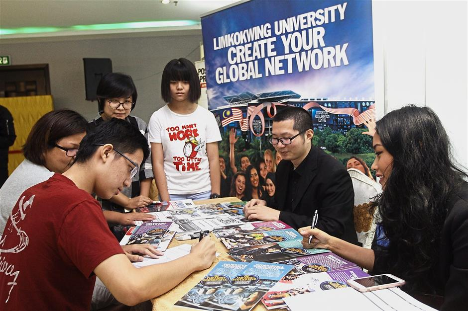 Kai Wei (in red) keen to know more about courses offered by Limkokwing University of Creative Technology.