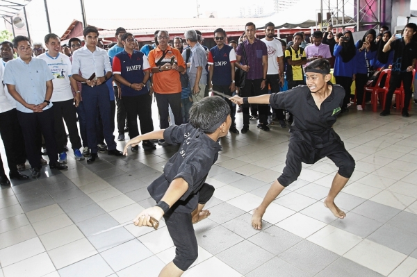 Visitors      watching a silat performance during the launch of the Penang Youth Festival at the Pesta Site in Sungai Nibong. — Photos: LIM BENG TATT/The Star