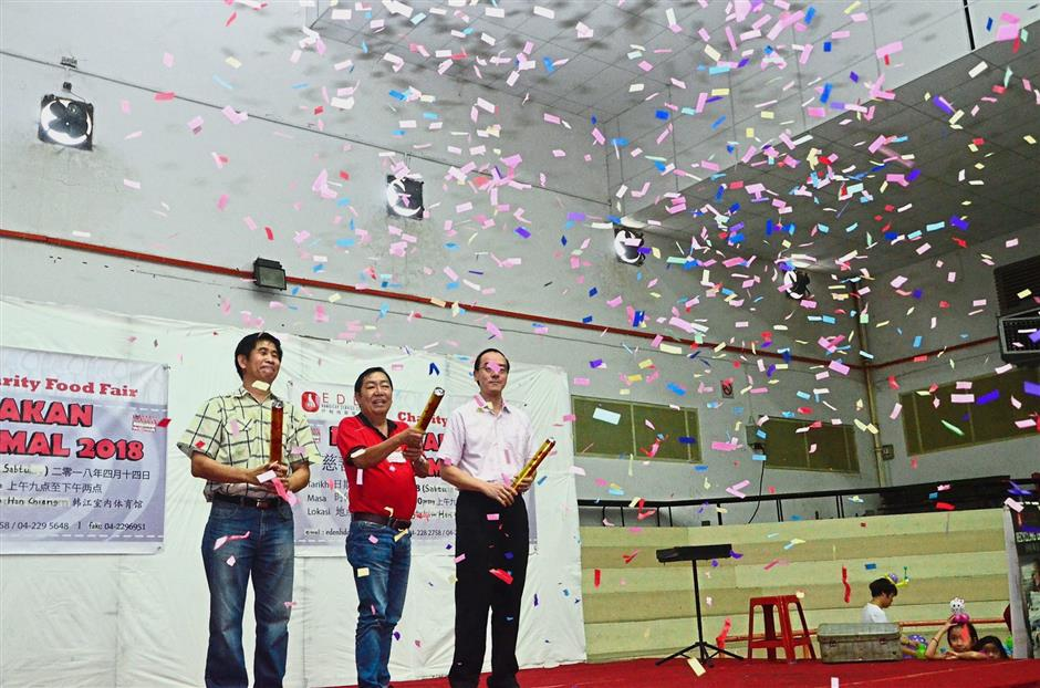 (From left) Khoo Tye and Tung releasing confetti to launch the charity food fair.