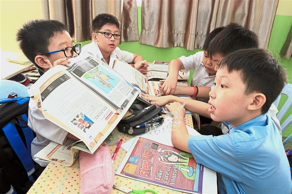 Pupils from SJK(C) Kampung Baru Ampang take a peek at the first issue of Step Up (Chinese) for 2019.