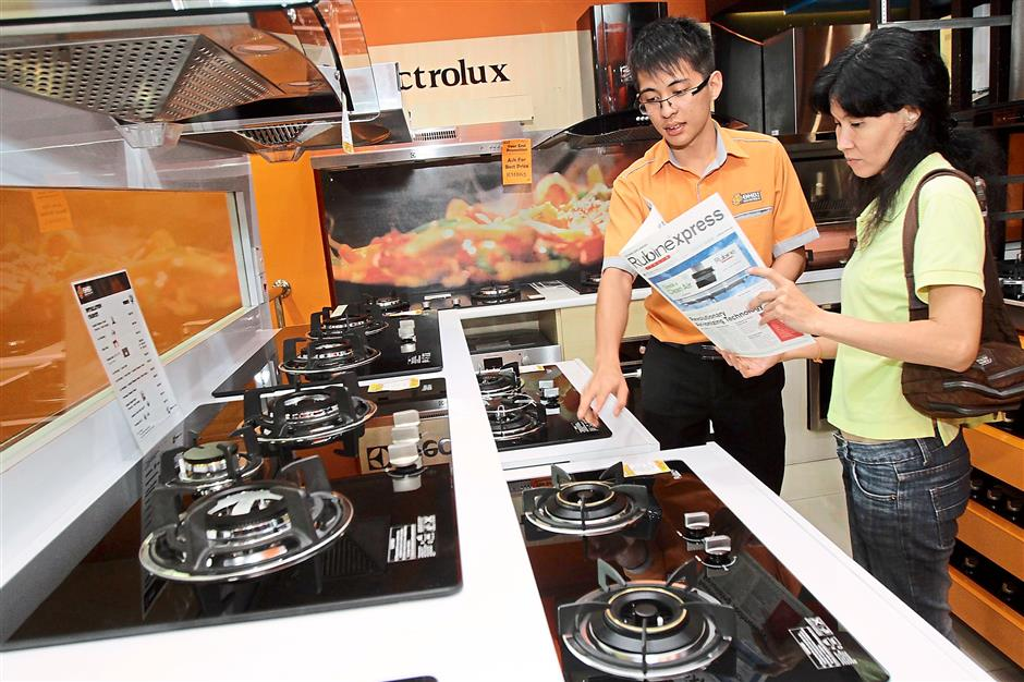 Ban Hin Bee salesman Raymond Phang showing stoves to a customer. Market research company GfK Retail And Technology Malaysia expects sales to rise closer to the implementation of GST.