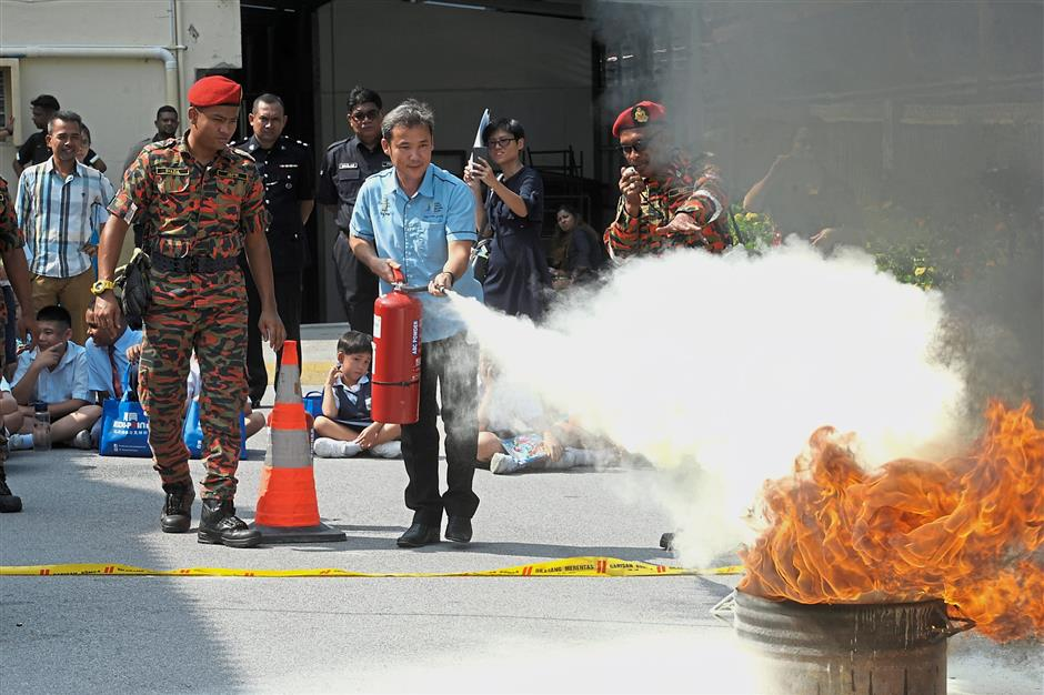 Yew assisting Fire and Rescue Department personnel during a fire extinguishing demonstration at SMJK Sacred Heart in Balik Pulau.