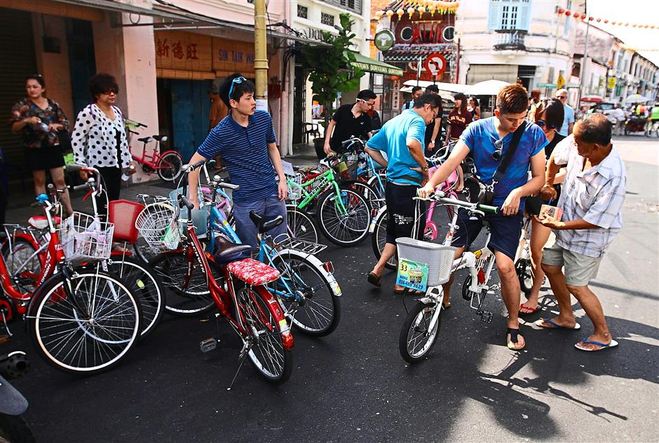Popular mode of transport: Tourists in George Town renting bicycles.