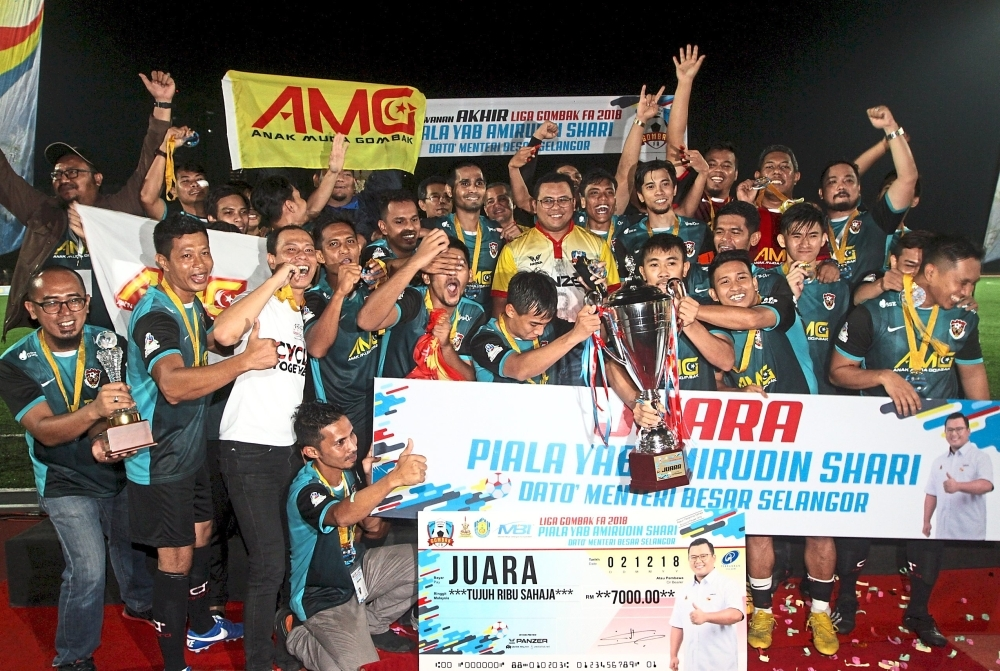 (Above) Amirudin (centre, in yellow) with the 2018 Gombak League champions AMG FC. u2014 Photos: M. AZHAR ARIF/The Star