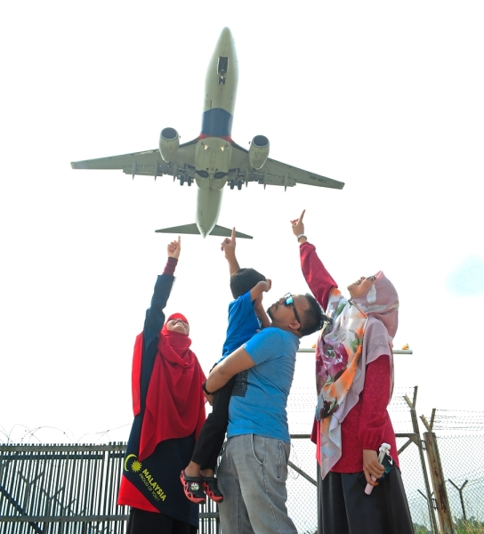 Azmi (centre) enjoying watching the planes land with his family. When the Antonov An-225 Mriya cargo plane landed in KLIA in 2016, he and his wife were at the lookout spot, complete with a picnic basket.