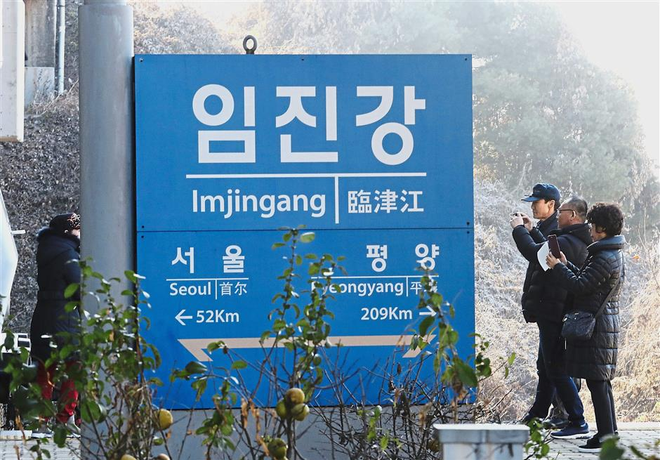 Iconic spot: People taking pictures near a signboard showing the distance to Pyongyang and Seoul from Imjingang Station in Paju. — AP