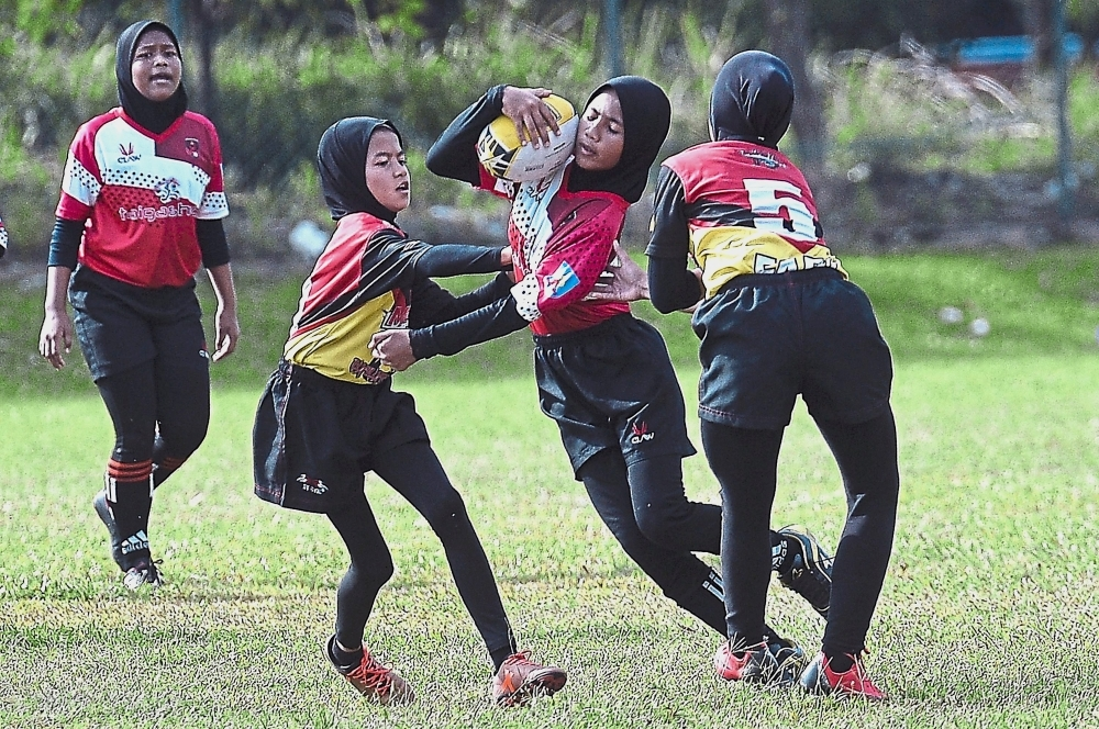 A Kota Bharu RA player (second from right) feeling the pressure from opponents in the finals of the Girls Under-12 category.