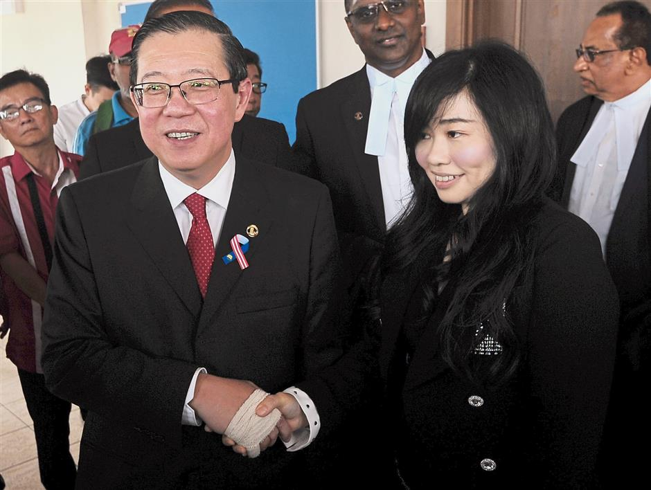 Relief: Lim and Phang shaking hands after their acquittal at the Penang High Court.  — Bernama
