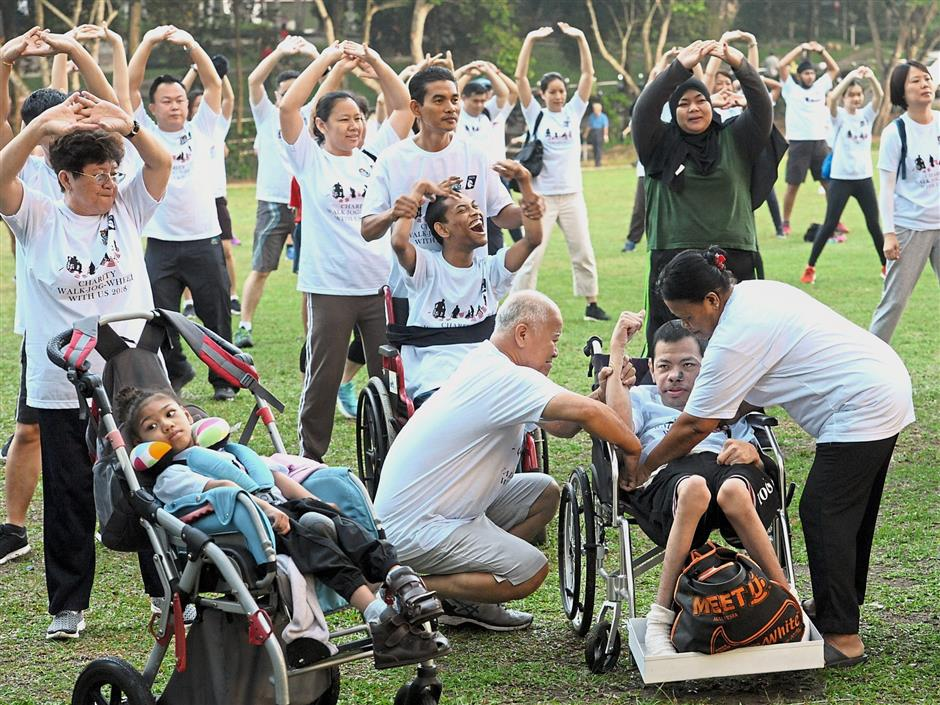 Disabled participants and others warming up before the 1.5km walk.