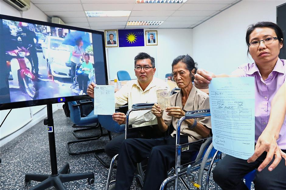 Chee Lin showing the summons issued by the council while Teoh holds the receipt at the press conference. With them is Teck Liang (showing Teoh's medical report).
