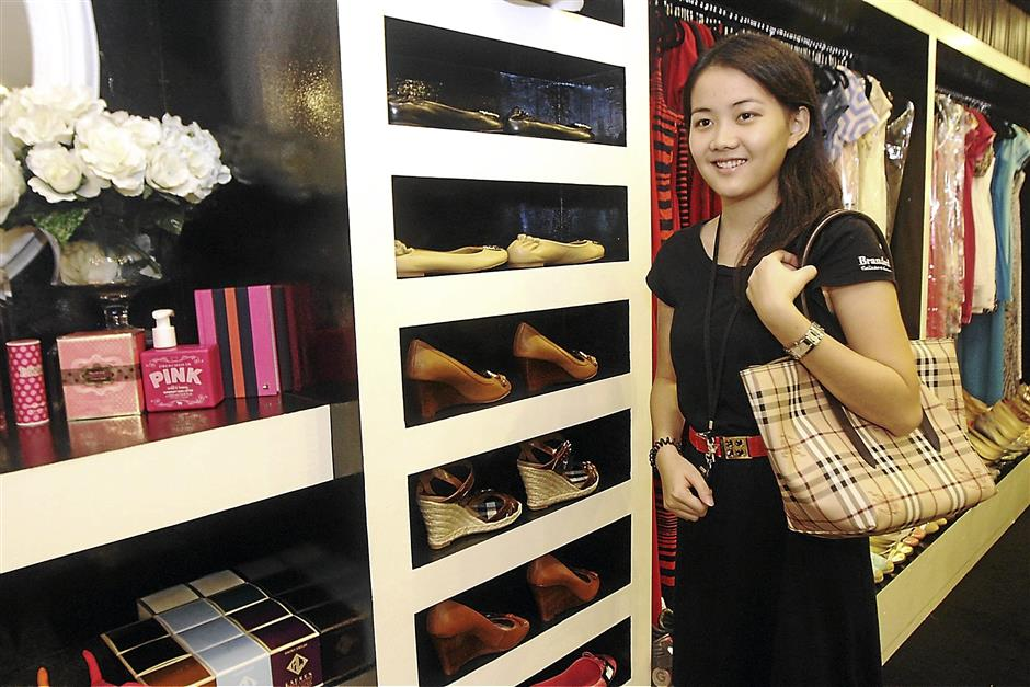 iplonline3009 3...A worker at Branded House Collection modelling one of the many designer handbags on sale at the store in Ipoh on Sept 27. On sale at the boutique are also designer shoes and clothing.