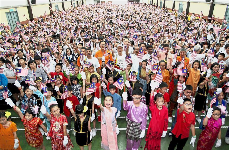 Patriotic pride: Pupils showing their Merdeka spirit together with AnakAnakMalaysia campaign representatives at SJK (C) Han Ming in Kuala Lumpur.