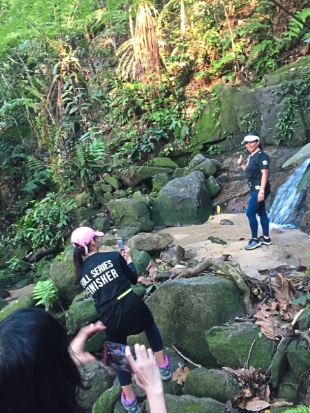 Participants stopping for photos at a waterfall along the trail.