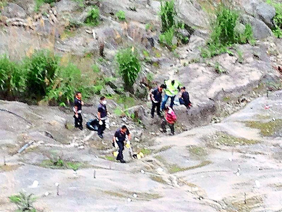 Gruesome task: Police officers looking for the body of the infant in Genting Highlands. The body was found and taken to hospital for a post-mortem.