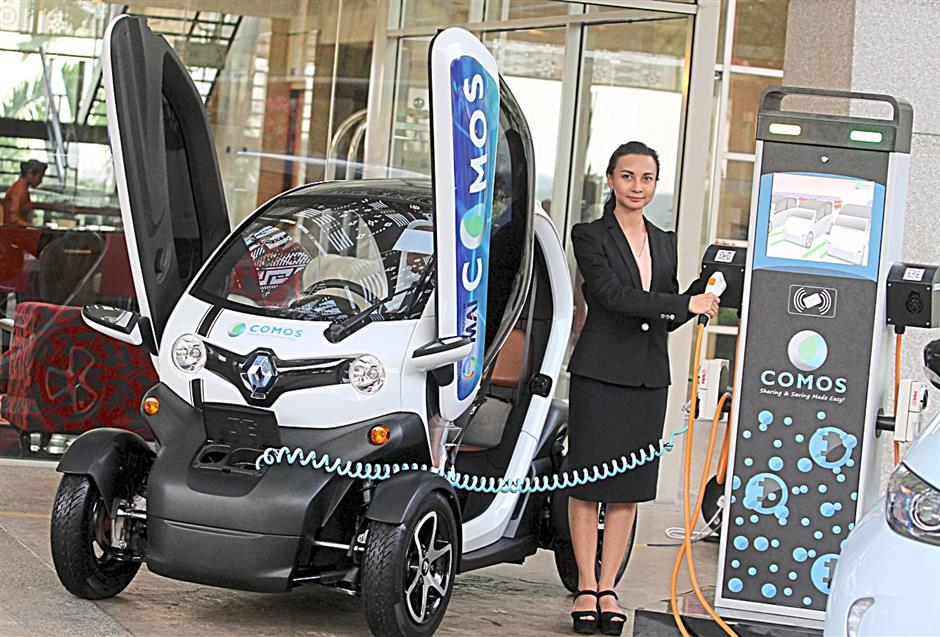 A model demonstrate how to charge the car after launching the new electric vehicle  called  'Renault twizy' during the soft launched of Malaysia's EV car sharing programme in Putrajaya.