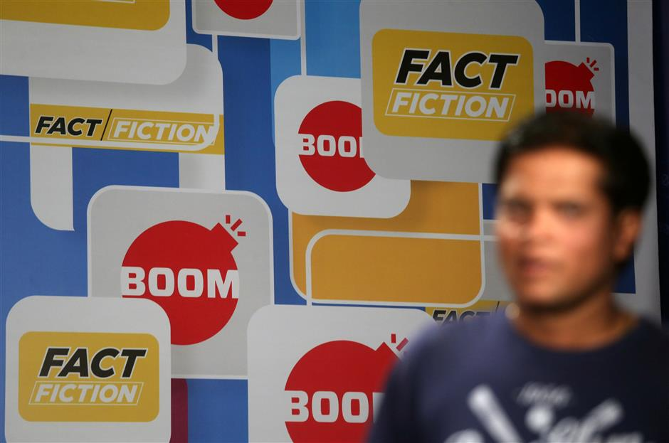 A crew member walks in front of a hoarding displaying the logo of BOOM, one of Facebook Inc\'s fact-checking partners in India, at a studio in Mumbai, India, March 12, 2019. Picture taken March 12, 2019. REUTERS/Francis Mascarenhas