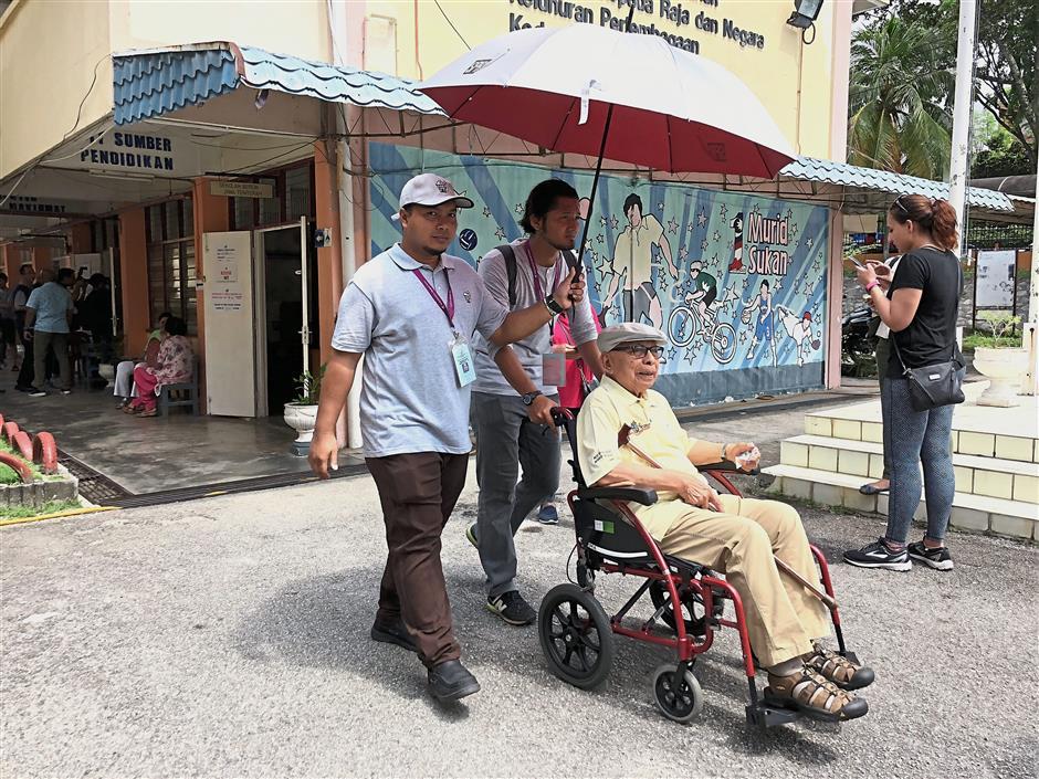 A wheelchair-bound senior citizen being escorted to his stream at SK Bukit Damansara.