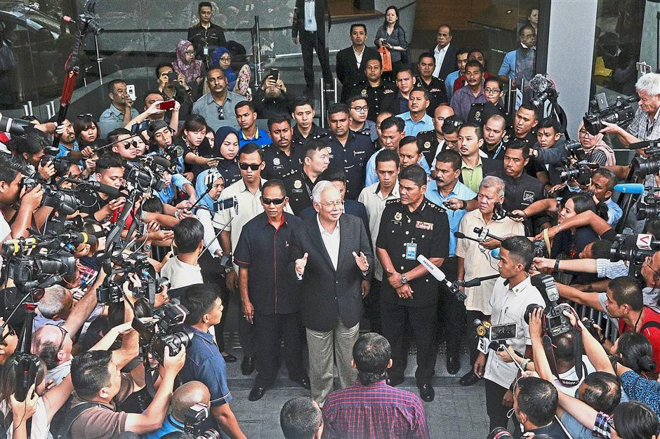 Sea of reporters: Najib speaking to pressmen on his way out of the MACC  headquarters in Putrajaya after a six-hour questioning session. — AP