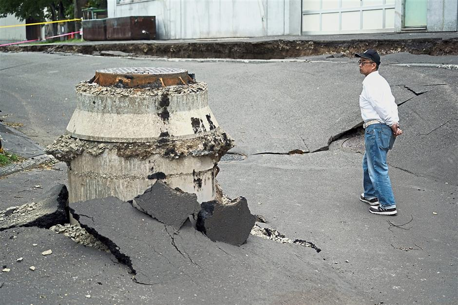FILE - In this Sept. 7, 2018, file photo, a neighbor walks by a manhole where the ground sank by an earthquake in Kiyota, outskirts of Sapporo city, Hokkaido, northern Japan. A magnitude 6.7 earthquake on Japanu2019s northernmost main island on Sept. 6 killed 41 people, most of them buried in a massive landslide. It wrecked roads and houses in the regional capital, Sapporo, and triggered a region-wide power outage. Local media cited Hokkaido Gov. Harumi Takahashi as saying the cost to public infrastructure, farming and forestry was estimated at 150 billion yen (1.3 billion), not including losses to tourism and private businesses. (AP Photo/Eugene Hoshiko, File)