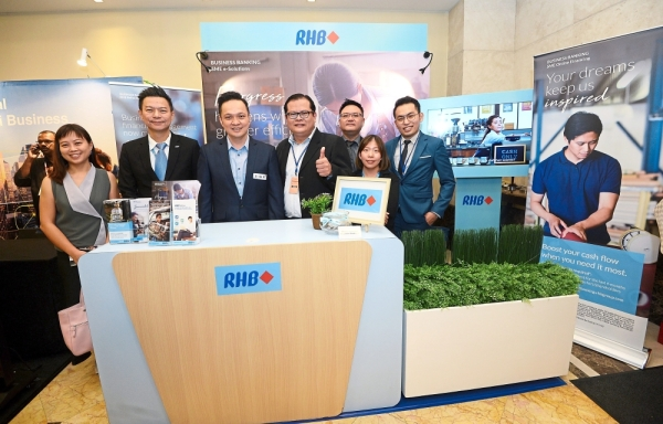 Yip (second from left) and RHB Banking Group chief marketing officer Abdul Sani Abdul Murad (third from left) with their team at the RHB booth.
