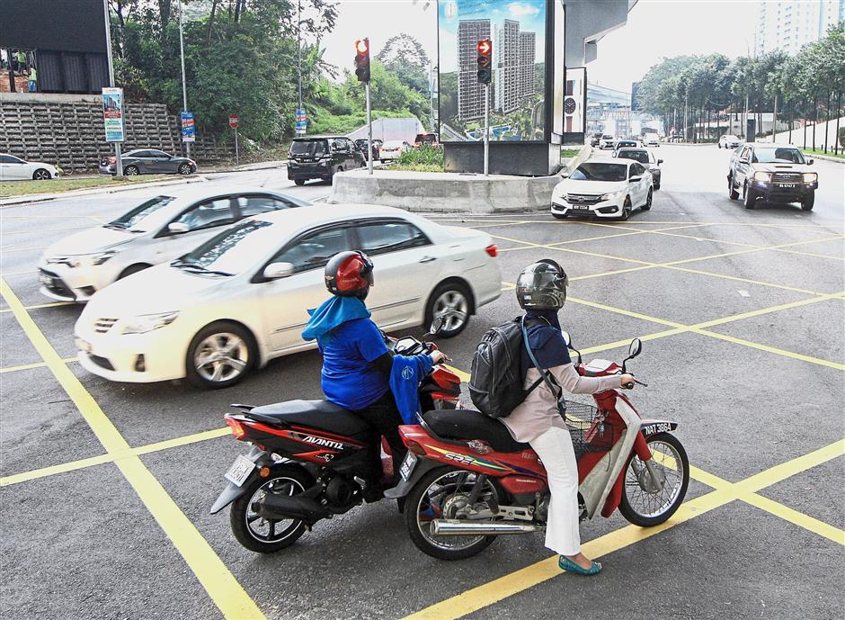 Two motorcyclists are seen here attempting to negotiate a right turn towards TTDI Plaza and TTDI Market. Some motorists are unaware that the traffic lights are in operations and accidentally run through the red lights.