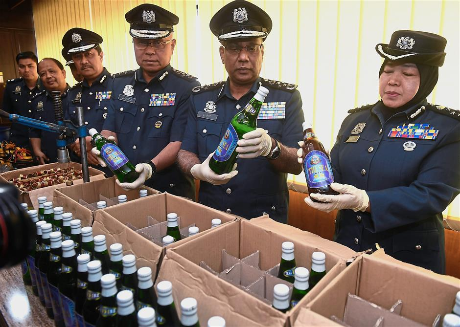 Looks real, but itu2019s not: Subromaniam (second from right) looking at a bottle with fake liquor at the KLIA Customs Department. u2014 Bernama