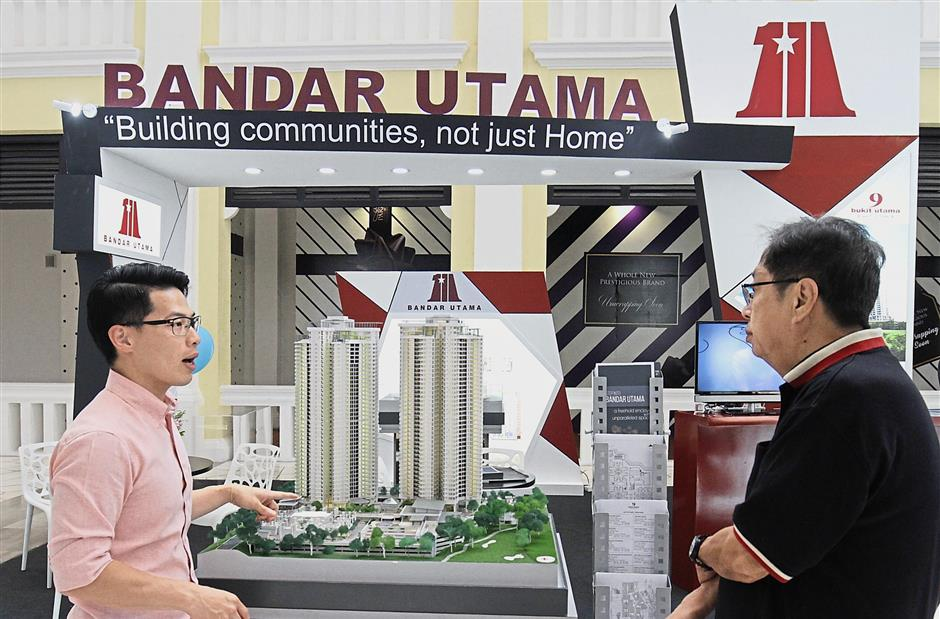 Sales and marketing representative Gary Teoh introducing The Effingham 9 Bukit Utama project at the Bandar Utama Development Sdn Bhd booth.