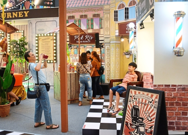 Visitors drawn to the nostalgic vibes of the 'Kota Raya Gurney' setup which features    a facade of             old-time shops.