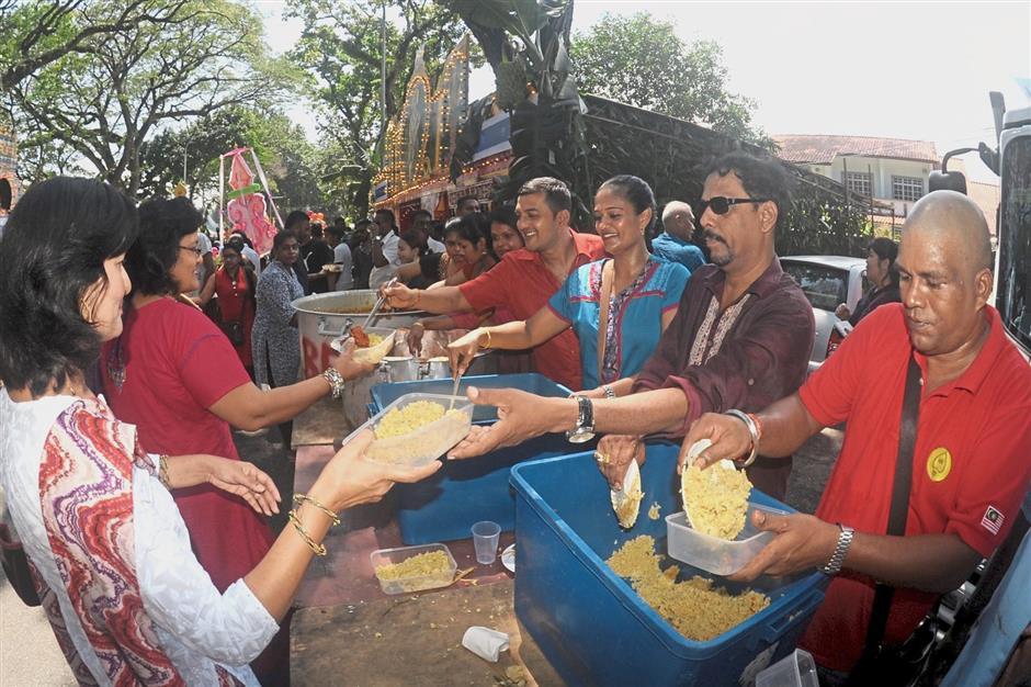 Malaysia Airlines staff members serving food outside their thaneer panthal in Jalan Utama.
