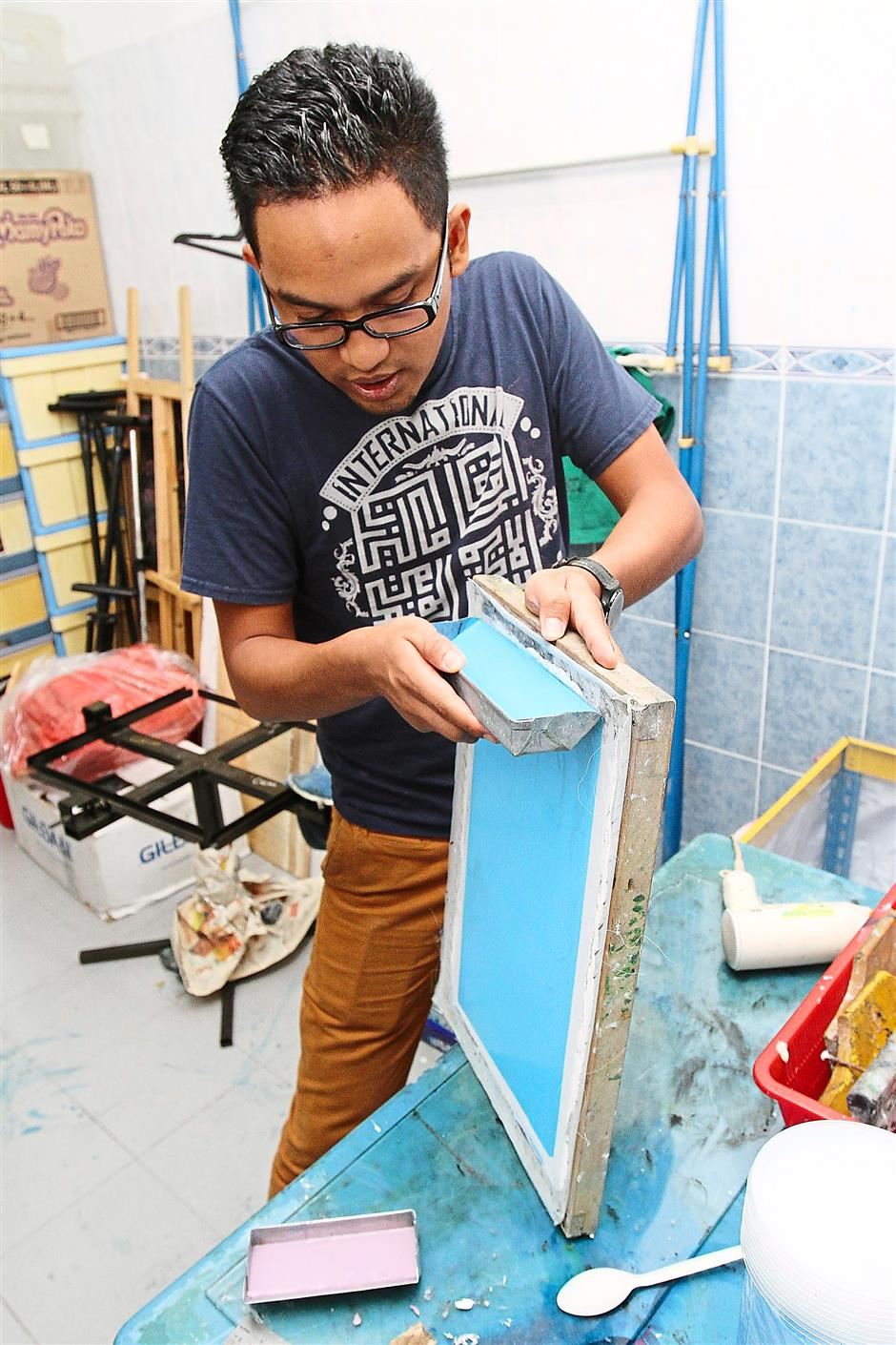 Doing well: Asyraf runs a successful T-shirt printing business from a makeshift bachelor pad.