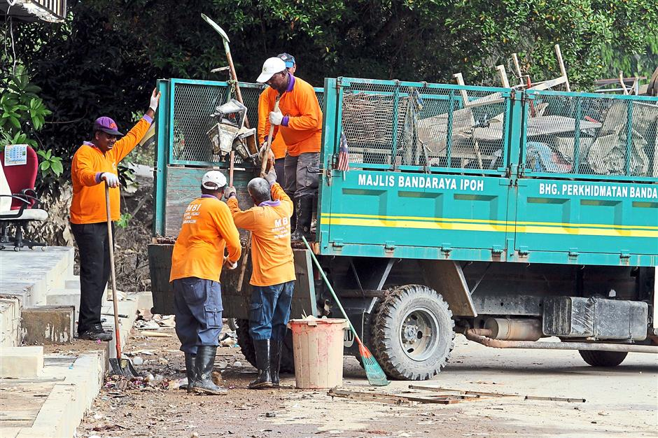 Sorting out the stuff: Kuala Kangsar council workers busy getting their equipment ready.