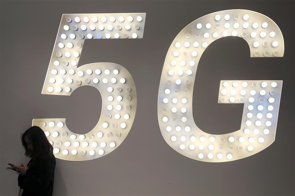 A woman looks at her mobile phone next to a 5G sign at the Mobile World Congress in Barcelona, Spain, February 25, 2019. REUTERS/Sergio Perez