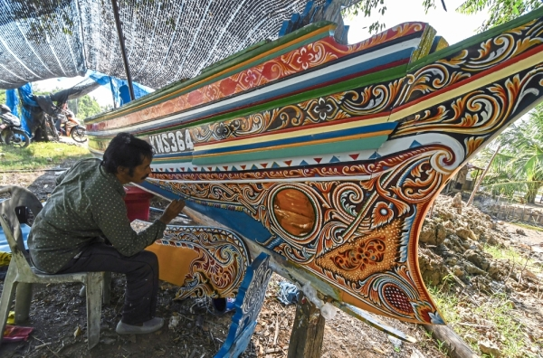 Intricate beauty: Mat Junuh working on one of the perahu kolek for his clients. u2014 Bernama
